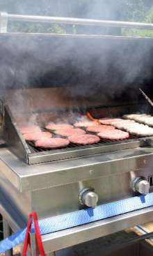 outdoor bbq catering grill showing burgers and brats photo.